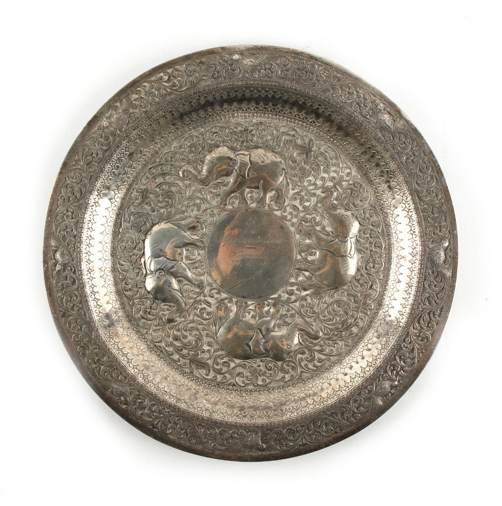 Lot 2 - An Indian white metal (tests silver) circular plate, decorated in repousse with elephants,