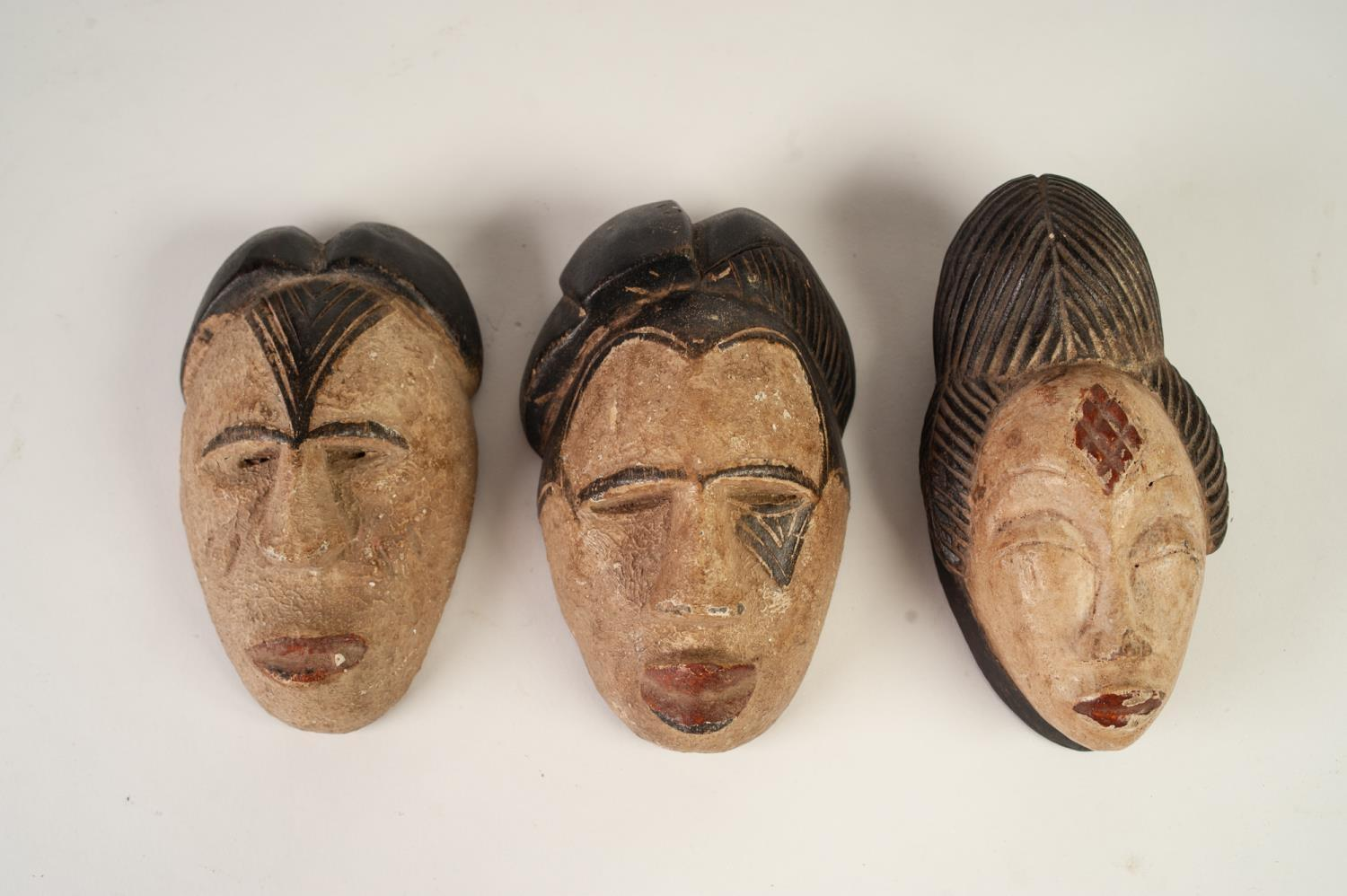 Lot 348 - THREE AFRICAN MINIATURE CARVED AND PAINTED WOODEN SOUVENIR TRIBAL MASKS (3)