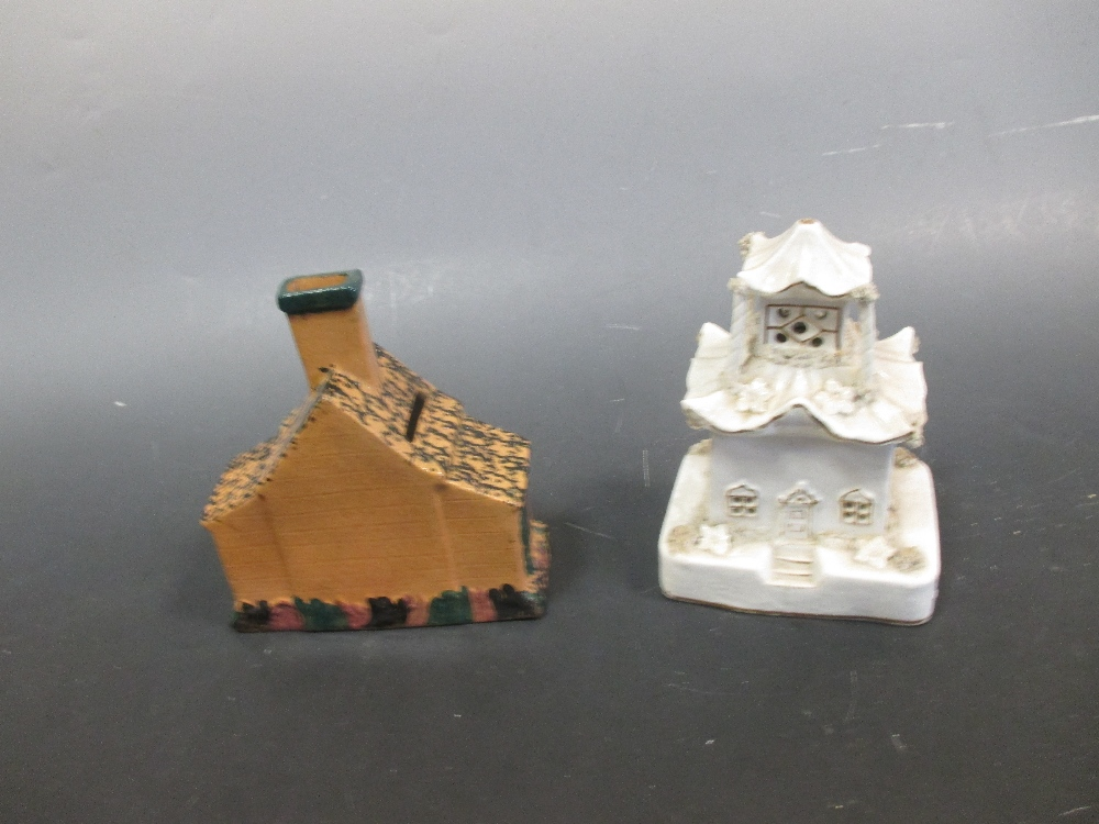 Lot 22 - A Staffordshire pastille burner and a money box in the form of houses (2)