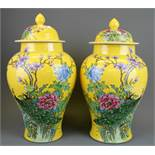 A pair of Chinese mid 20th Century hand enamelled jars and lids decorated with birds and flowers, H.