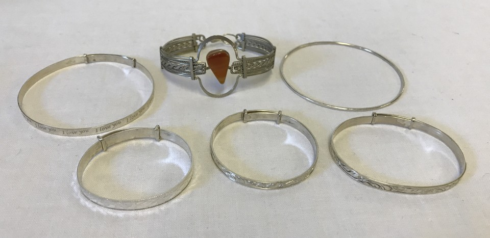 Lot 1046 - A collection of 6 silver/white metal bracelets.