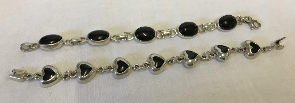 Lot 1027 - 2 heavy silver bracelets, both set with black stones.