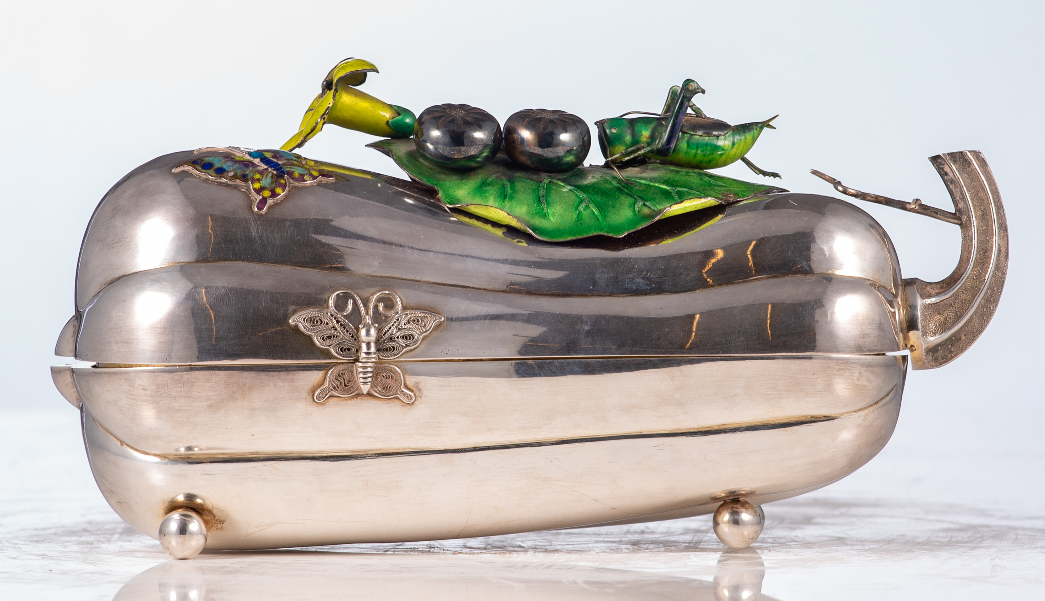 Lot 5 - An Oriental silver pumpkin shaped box and cover, with enamelled alto relievo decoration depicting