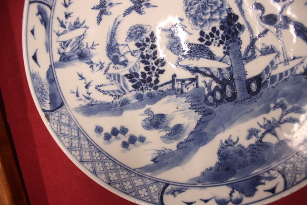 Lot 12 - An 18th Century Chinese blue and white plate, the body profusely decorated with exotic birds and