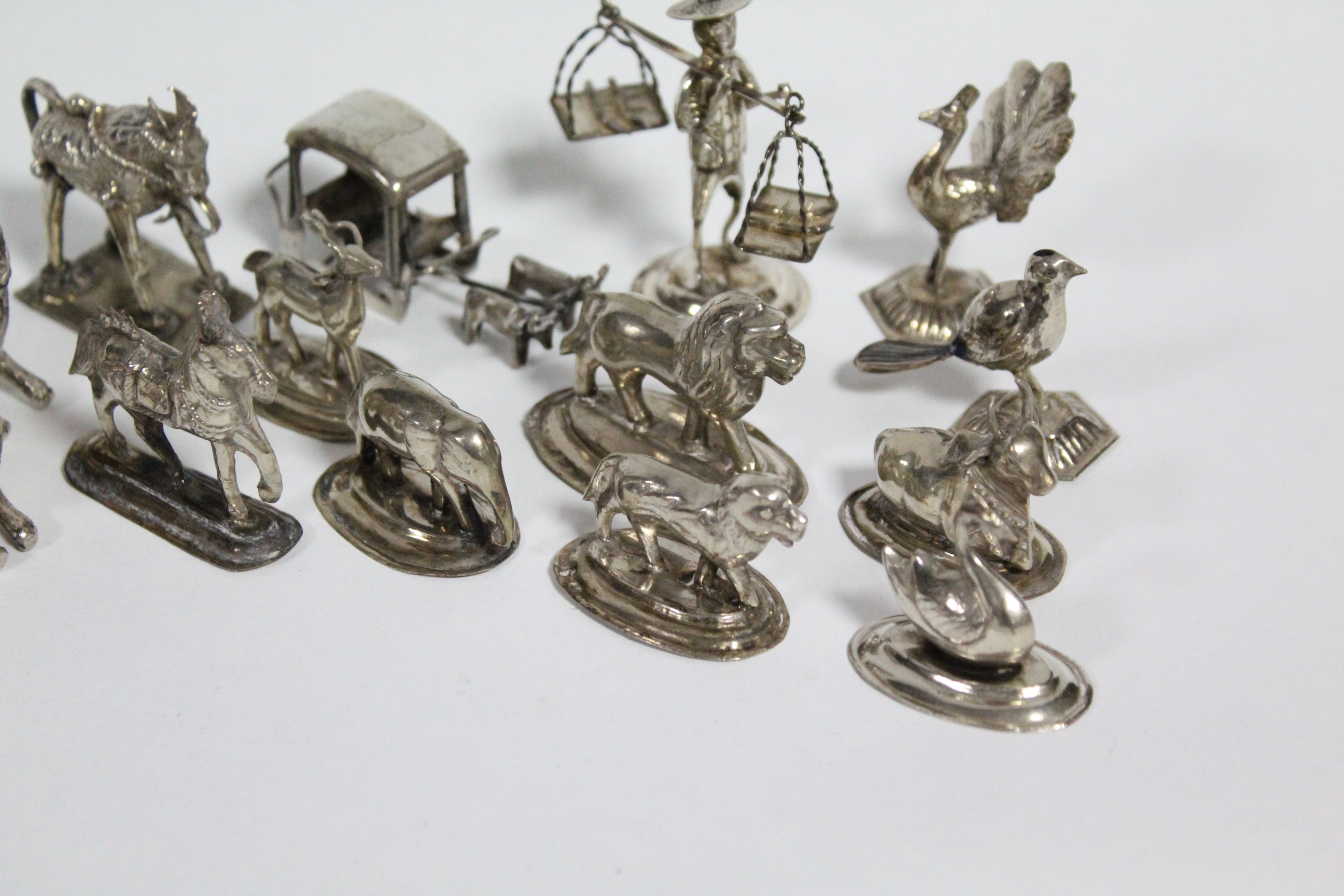 """Lot 13 - Twelve various Eastern white metal small models of animals & birds, the tallest: 1¾"""" high; a ditto"""