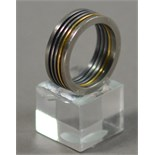 JOEL DEGEN (born 1944); a ring, stainless steel and titanium combined with 18ct gold, ring size Q.