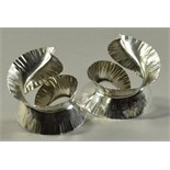 RAUNI HIGSON (born 1970); a pair of hallmarked silver napkin rings of spiral feather form, London