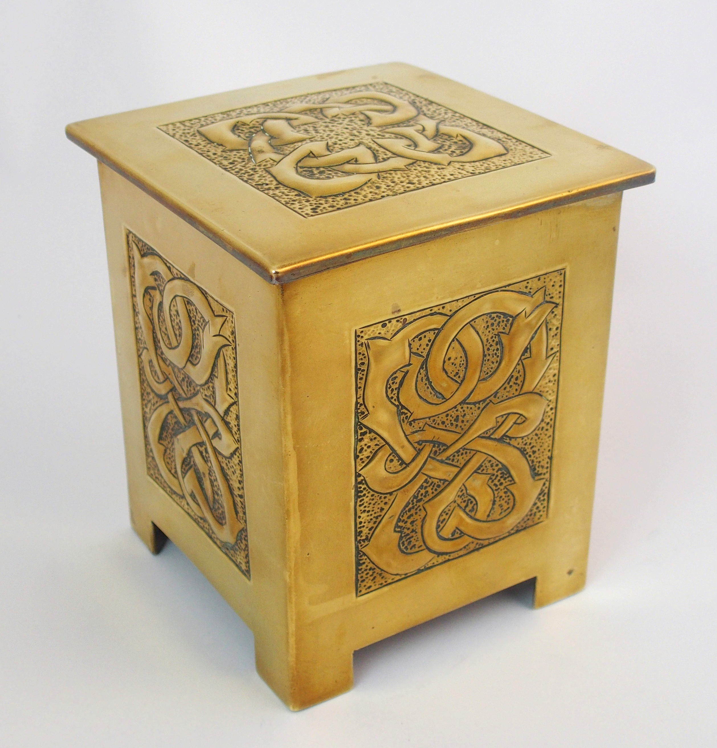A Celtic revival brass tea caddy in the style of Alexander ...