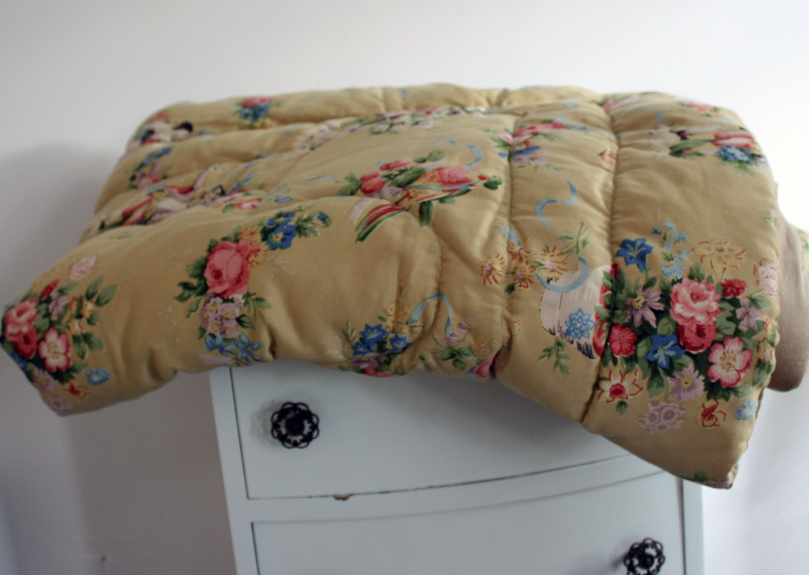 Vintage 1950s or earlier feather eiderdown/quilt. Measures 58 inches x 43 inches.