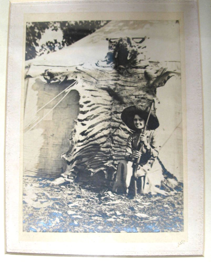 Lot 20 - [BIG GAME] framed photograph of armed woman hunter in the field, tiger-skin in background, f &g, ca.