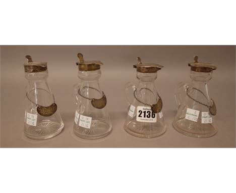 A collection of four silver mounted glass whisky noggins, in a variety of designs, all Birmingham 1911, differing makers, wit