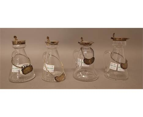 A collection of four silver mounted glass whisky noggins, in a variety of designs, differing makers and dates, with four whis
