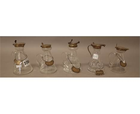 A collection of five silver mounted glass whisky noggins, in a variety of designs, with five whisky noggin labels as fitted,