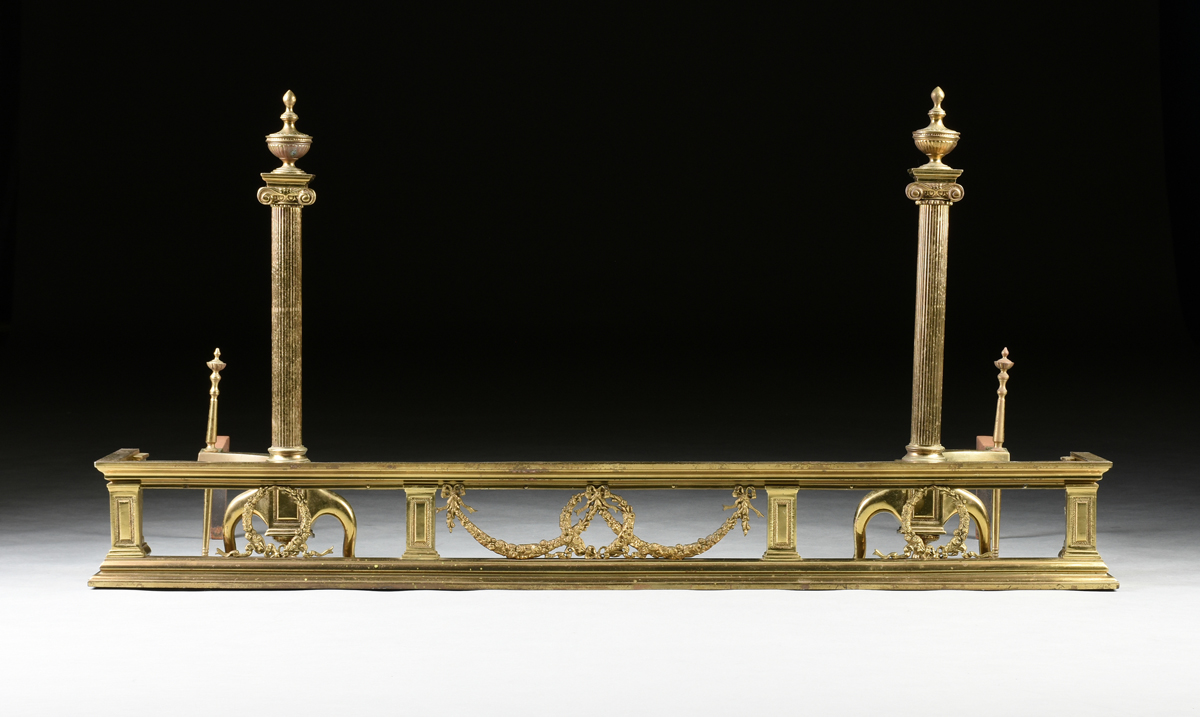 Lot 50 - A PAIR OF FEDERAL STYLE POLISHED BRASS FIREPLACE ANDIRONS AND FENDER, 20TH CENTURY, the Ionic reeded
