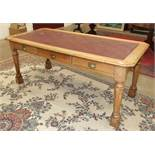 A Late-Victorian oak library table, the top inset with writing surface above three drawers, on