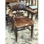 An early-19th century mahogany library chair, the open curved back and padded arms on carved