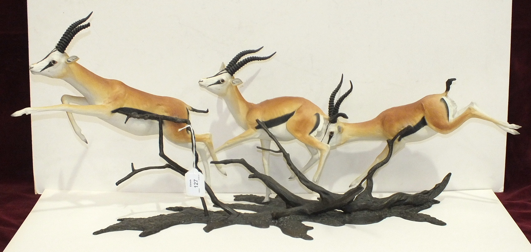 Lot 127 - American, 20th century, a trio of finely-detailed porcelain gazelles bounding through a bronze