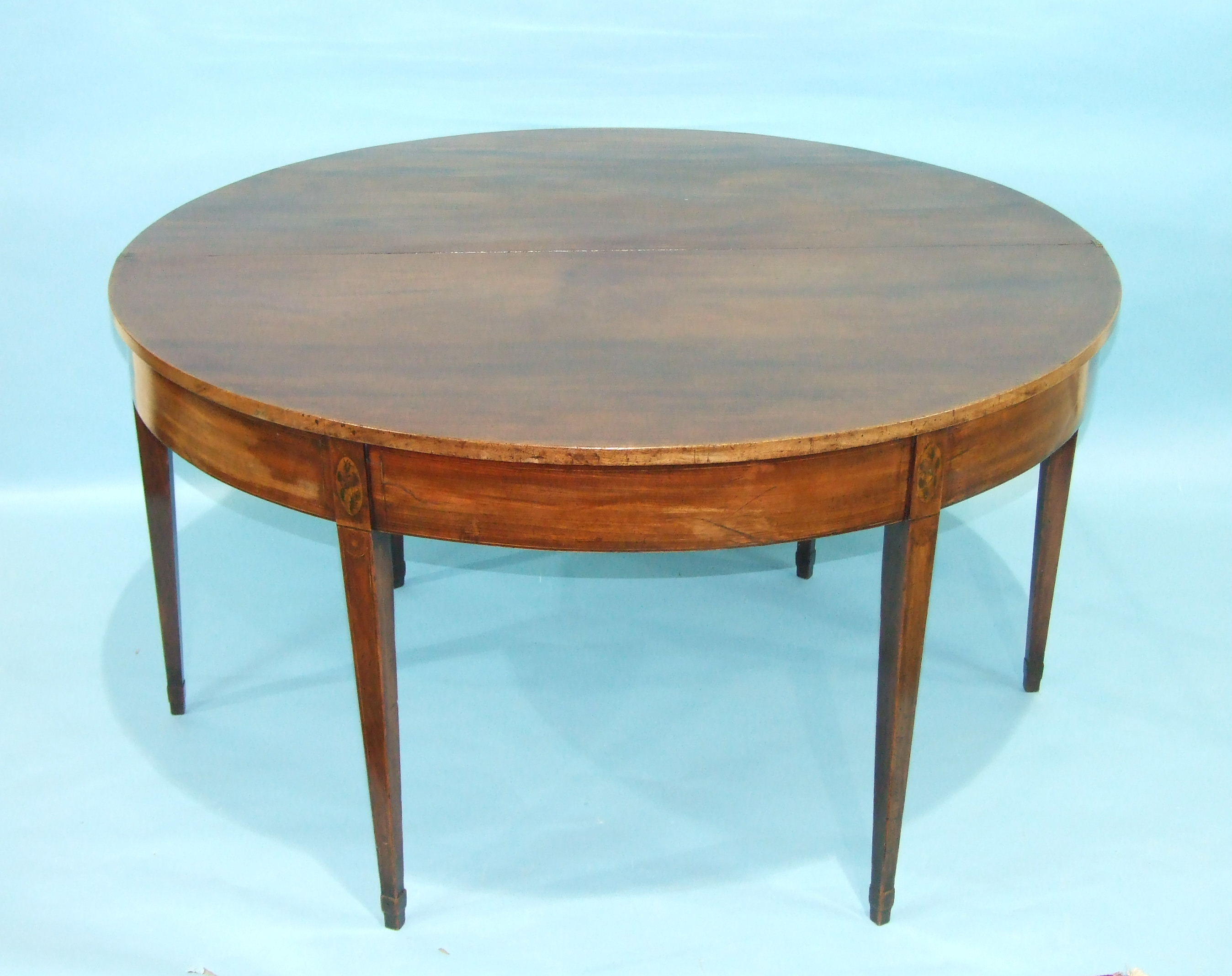 A Georgian mahogany gate-leg breakfast table, the circular fold-over top with inlaid shell motif, on