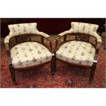 A pair of Edwardian walnut-framed low armchairs, each with upholstered back, arms and seats, on