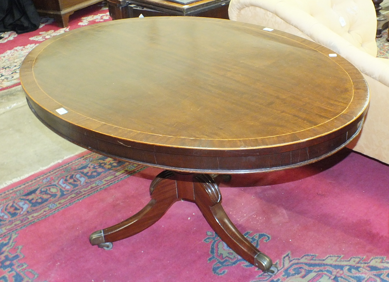 A 19th century mahogany oval tilt-top breakfast table on turned column and hipped sabre legs with