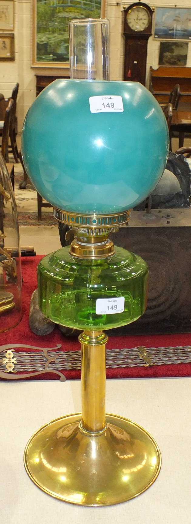 Lot 149 - A late-19th/early-20th century oil lamp, the green glass reservoir on brass column and circular