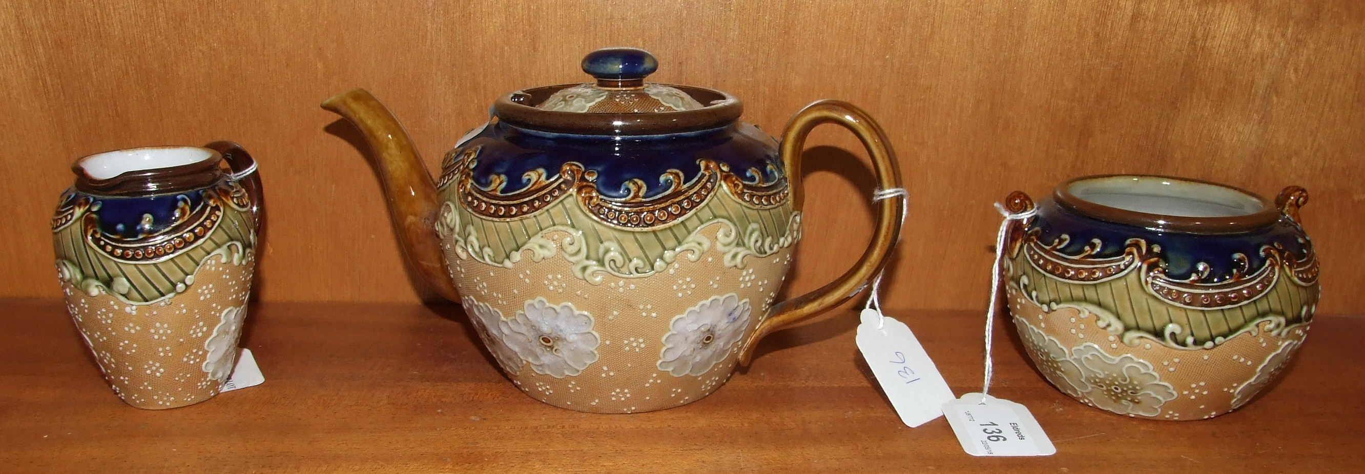 Lot 136 - A Royal Doulton stoneware three-piece tea service decorated with flowers on a pale ground, within