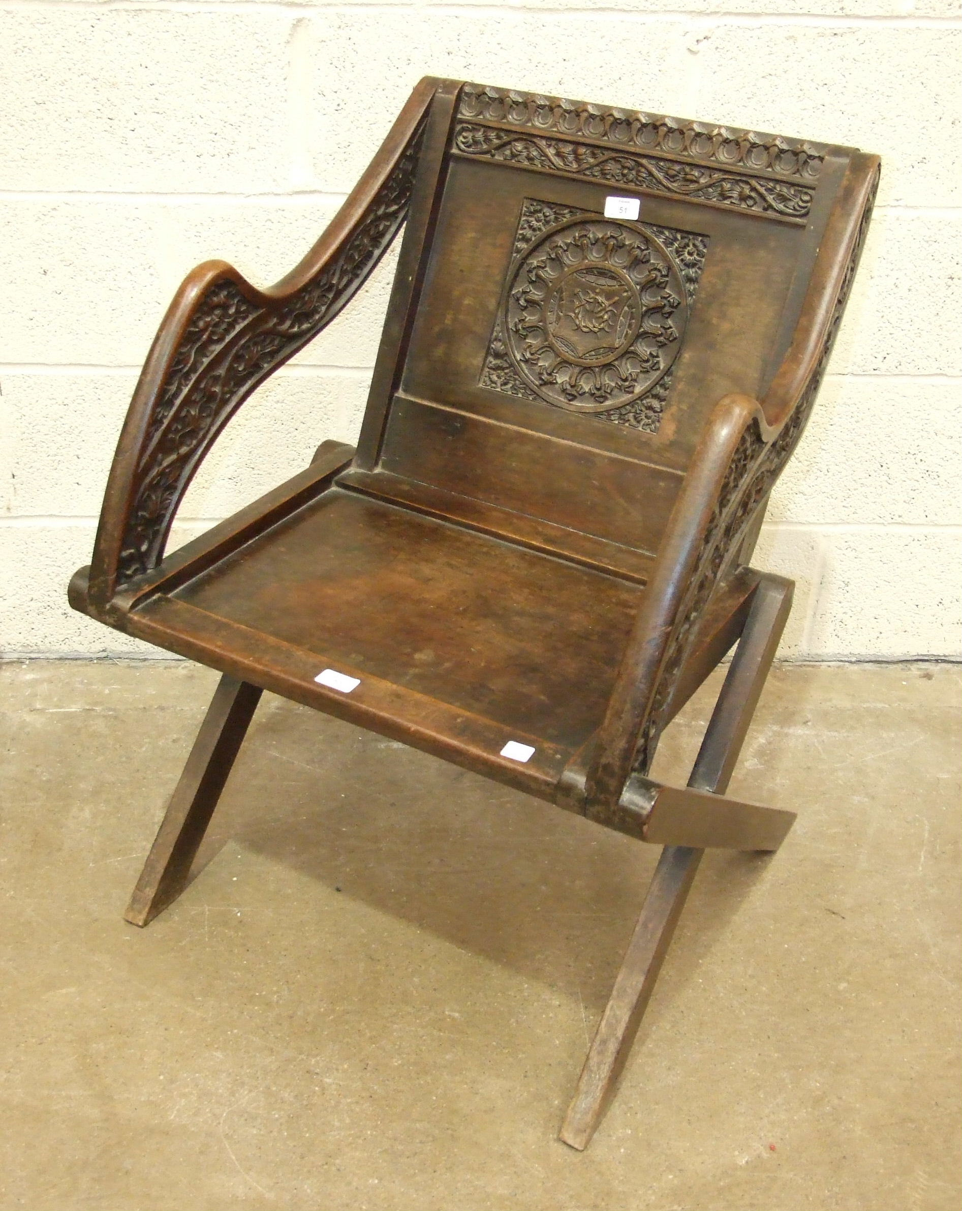 A copy of a mid-16th century hardwood folding chair, on X-frame, with carved back and arms, 87cm