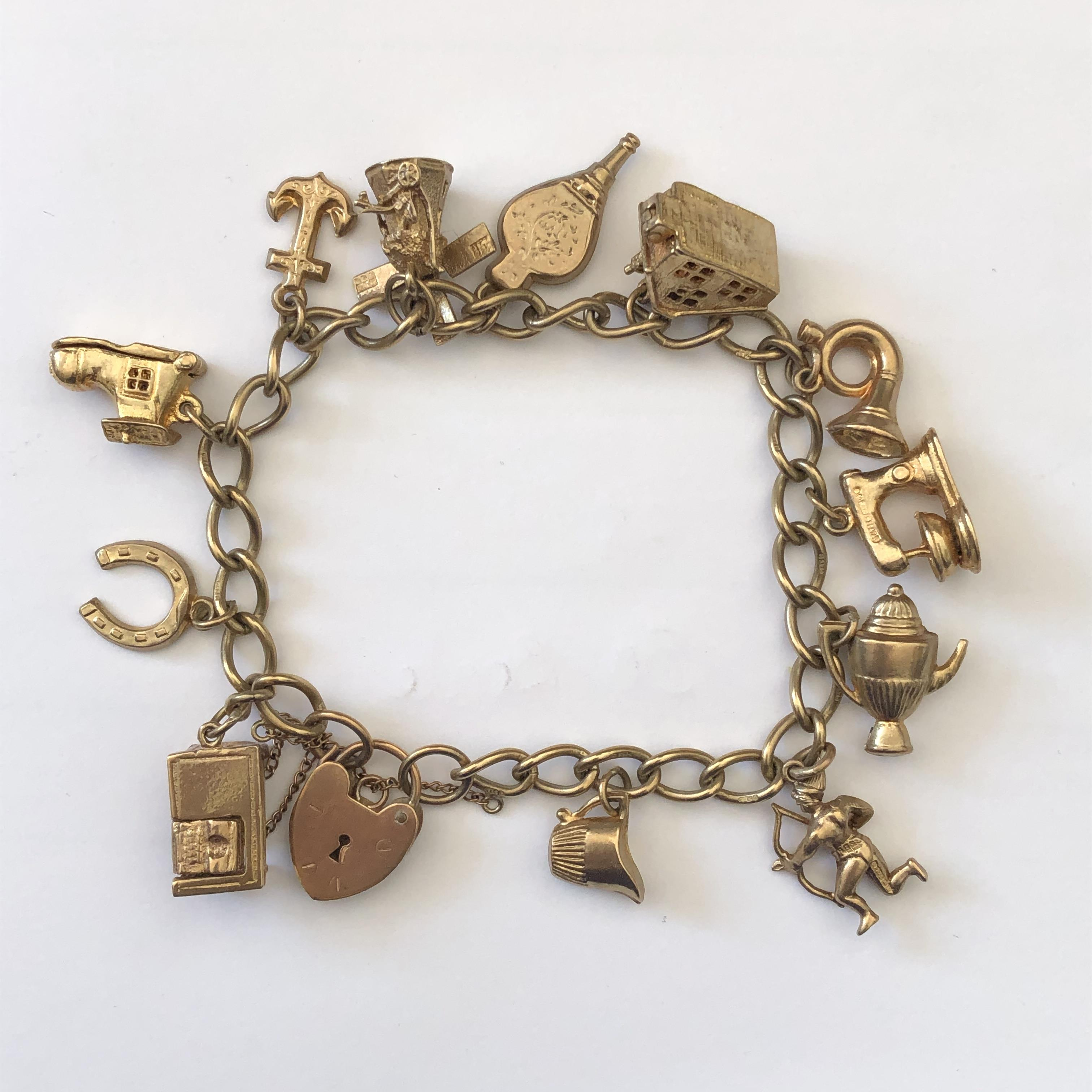 Lot 203 - 9CT GOLD BRACELET WITH VARIOUS CHARMS AND HEART PADLOCK CLASP 28.