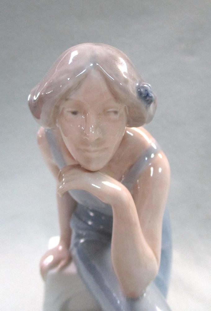 Lot 47 - A Royal Copenhagen model of a woman, seated on a pedestal, dressed in evening wear with a flower