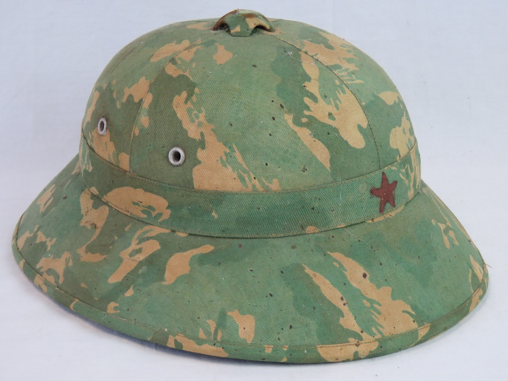 Lot 27 - A North Vietnamese Army (NVA) camouflage pith hat having Indo-China camo with chin strap.