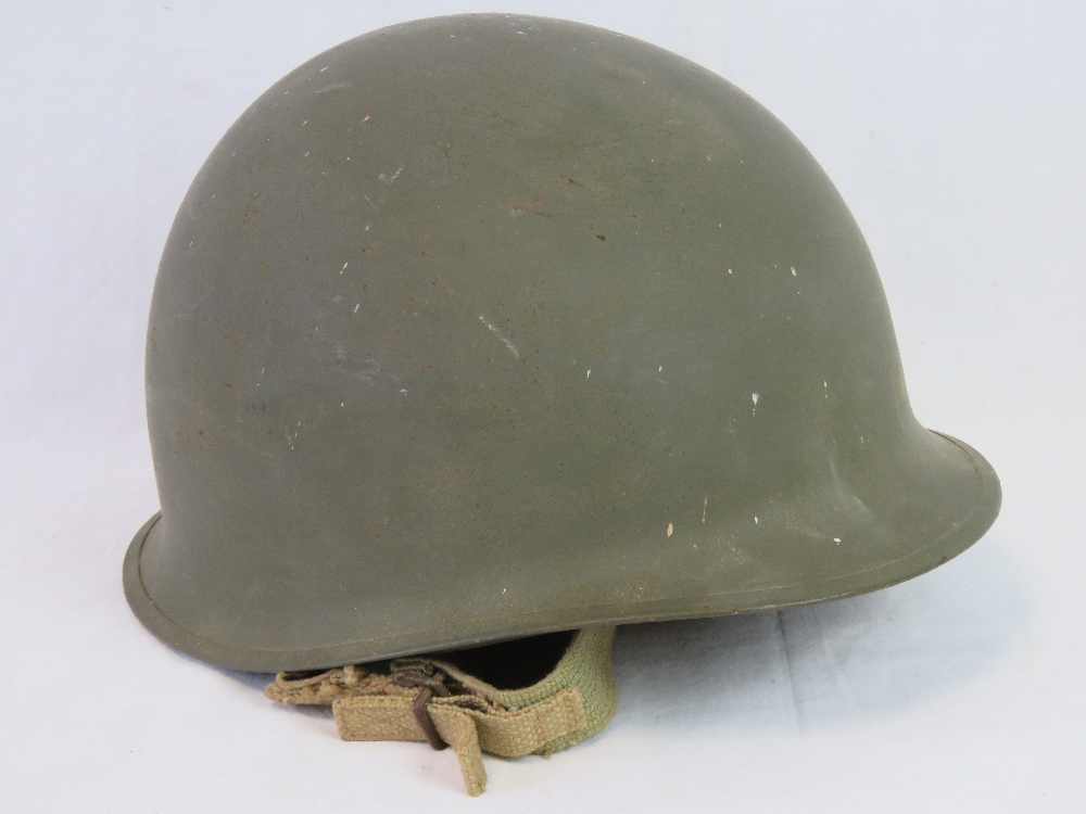 Lot 58 - A US WWII M1 Infantry issue helmet with original liner and chinstrap having plain olive drab paint,