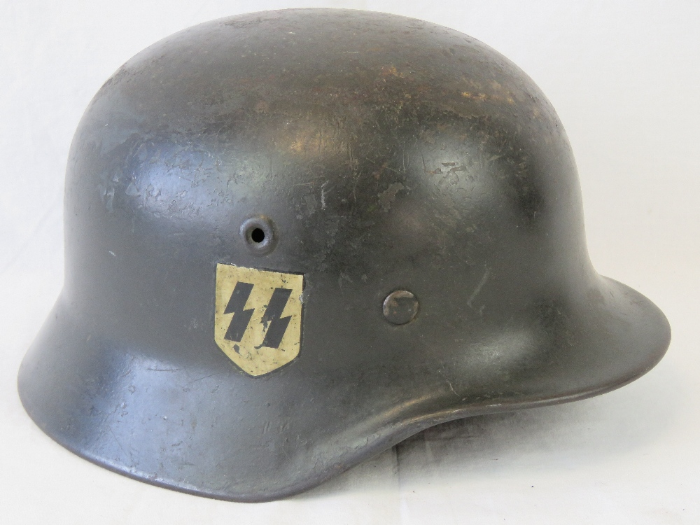 Lot 51 - A WWII German SS helmet, having two decals upon,
