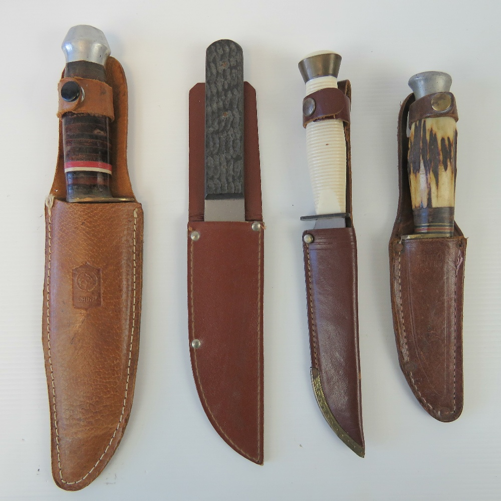Lot 41 - Four hunting knives; two with Sheffield steel blades, each having leather sheath.