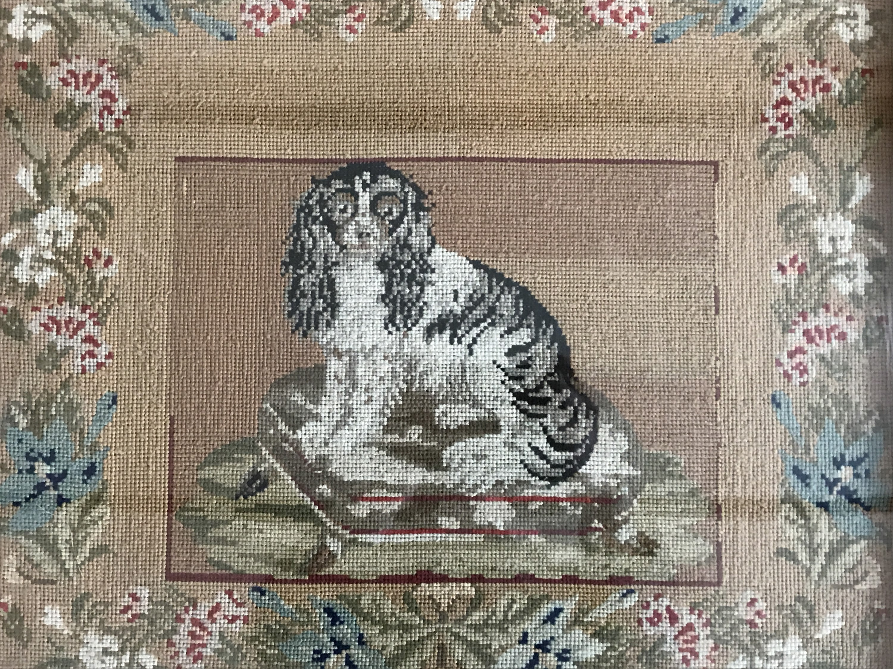 Lot 37 - A Victorian woolwork gros point embroidery of a spaniel seated on a footstool, in a running floral