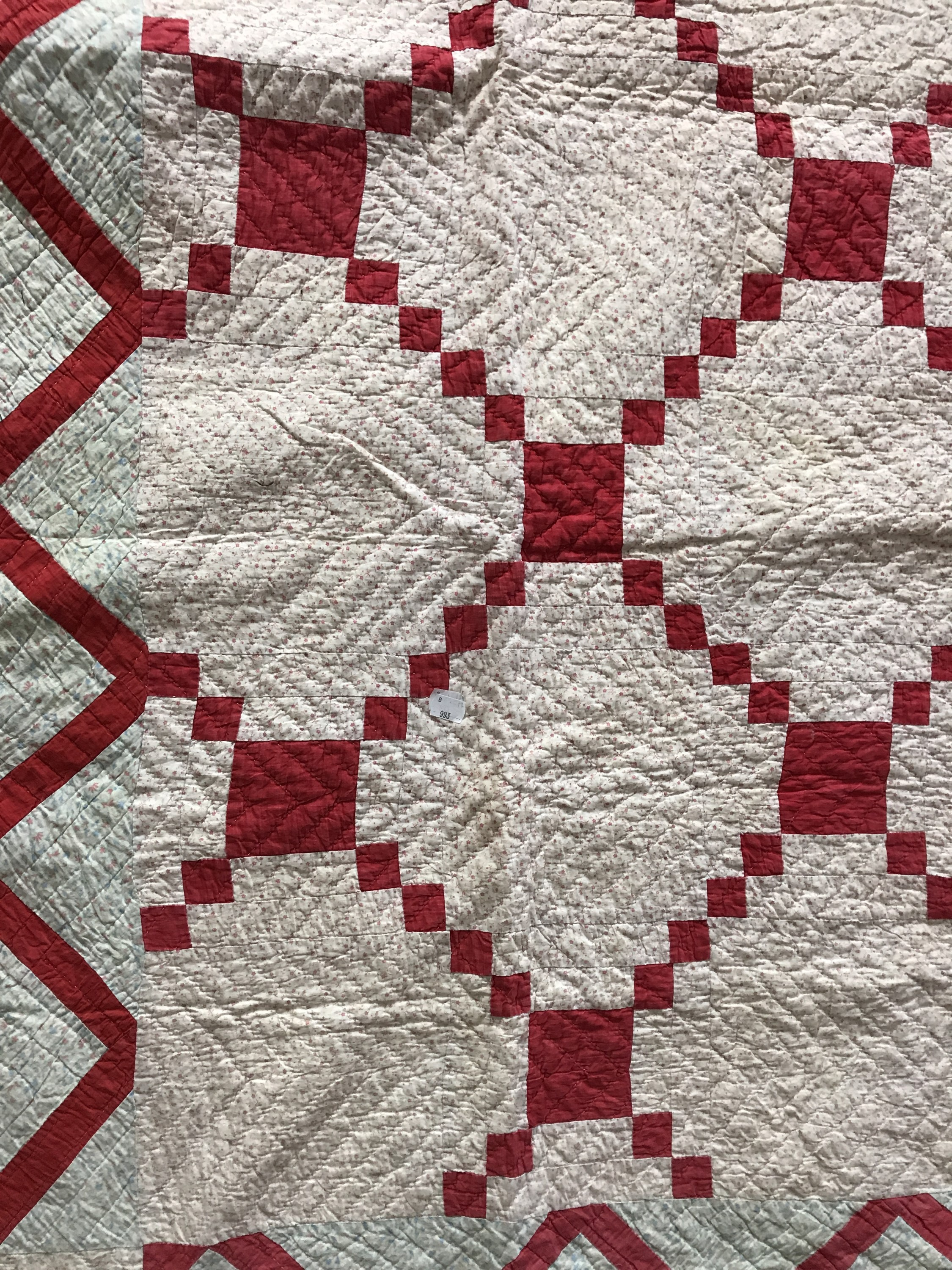 Lot 35 - An early 20th Century patchwork quilt, in a geometric diaper design incorporating red cotton over