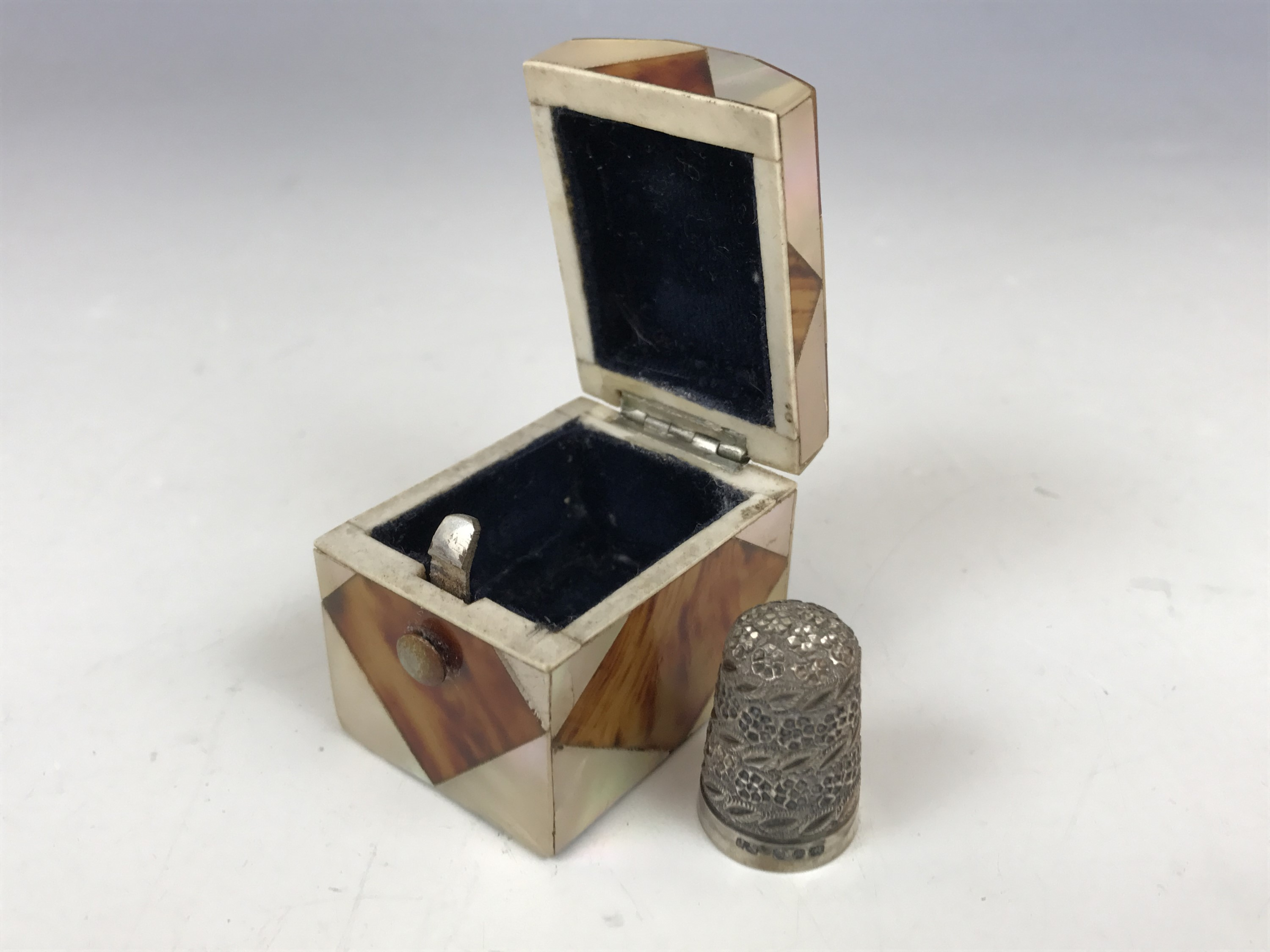 Lot 5 - A 19th Century mother-of-pearl and tortoiseshell veneered thimble case and later silver thimble