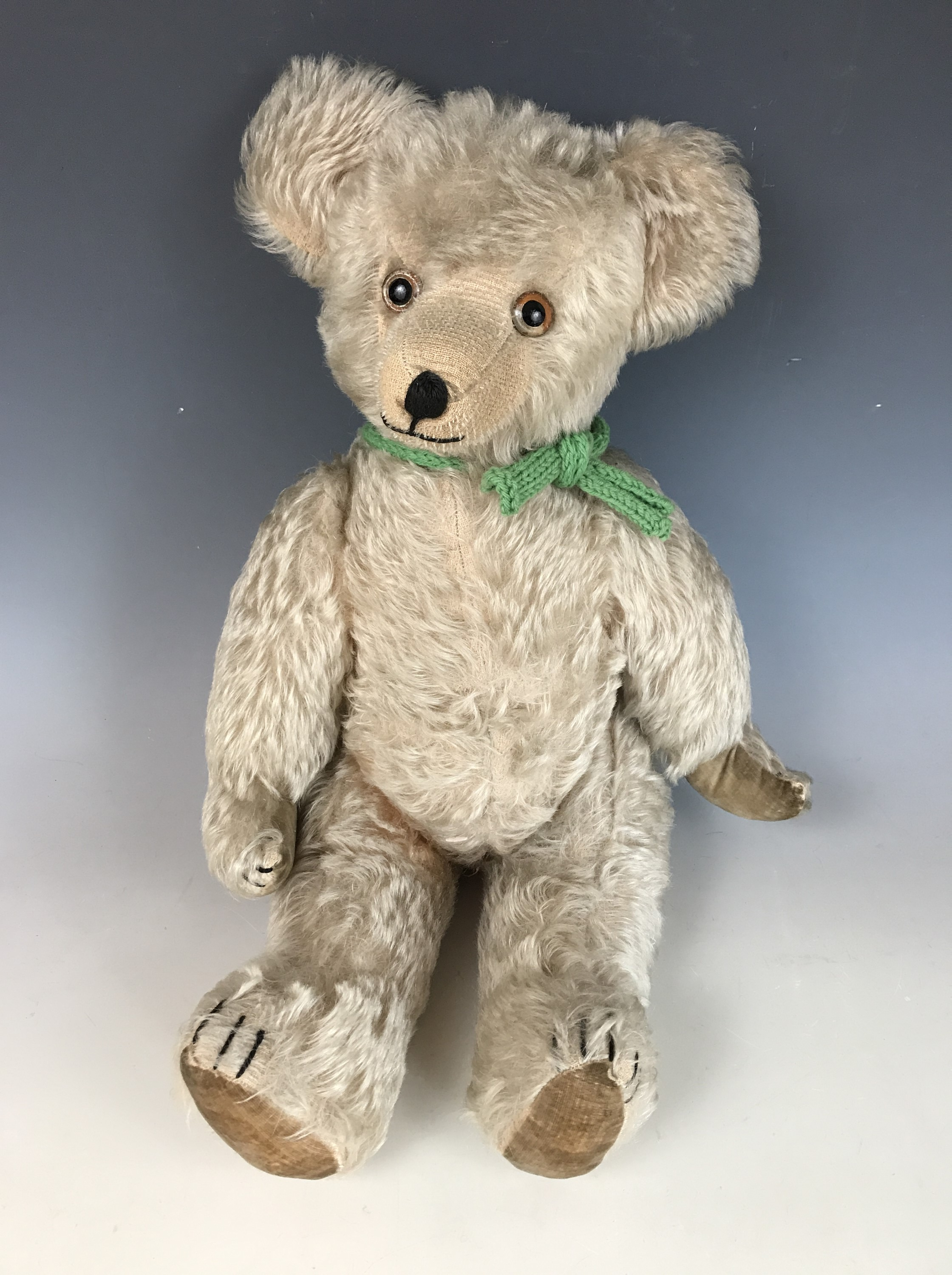 Lot 43 - A 1930s Teddy bear, with wood wool stuffing, articulated limbs, blonde mohair, velvet lined pads and