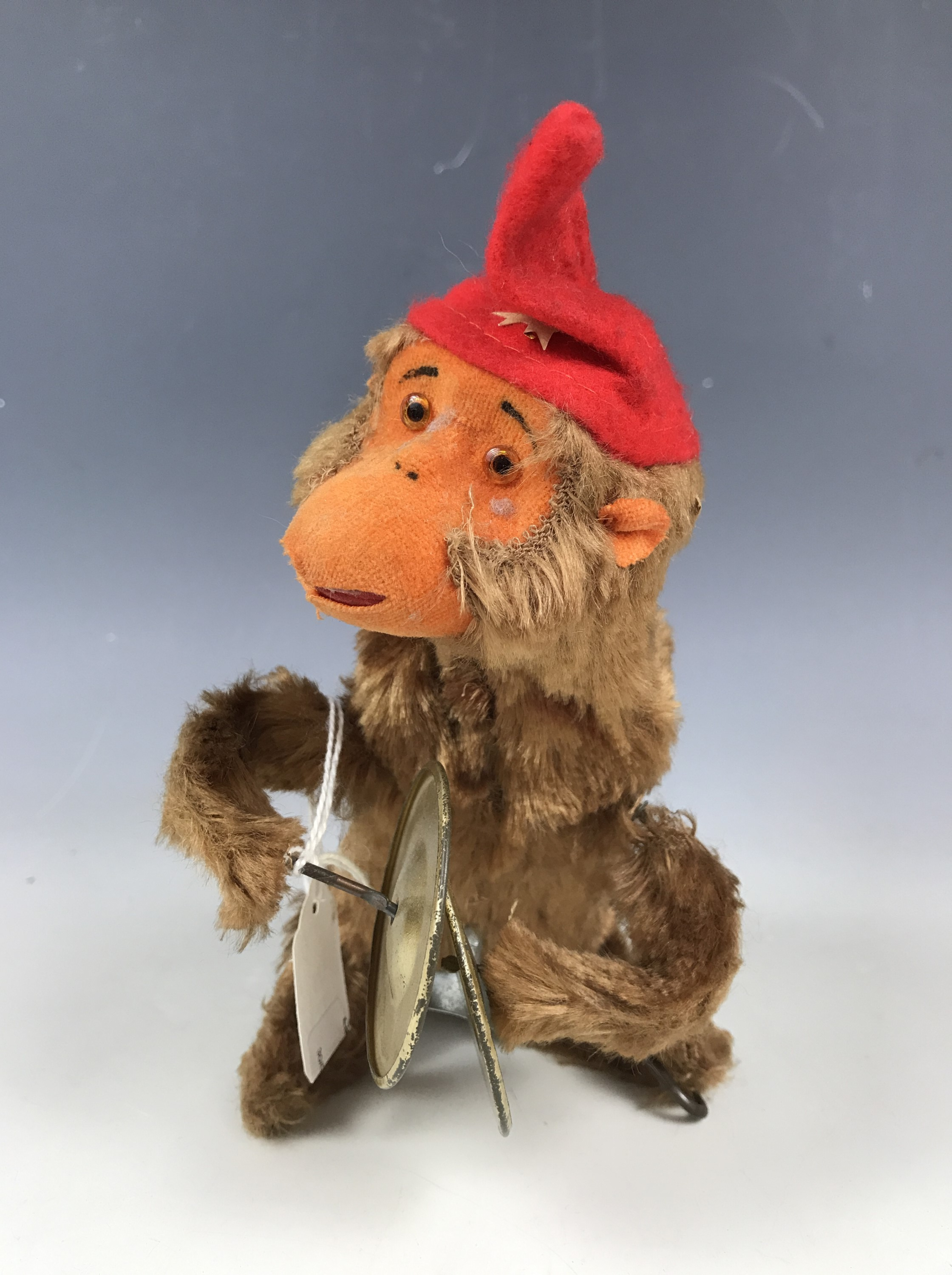 Lot 55 - A mid 20th Century clockwork automaton toy monkey playing the cymbals, 16 cm, with lower stage of