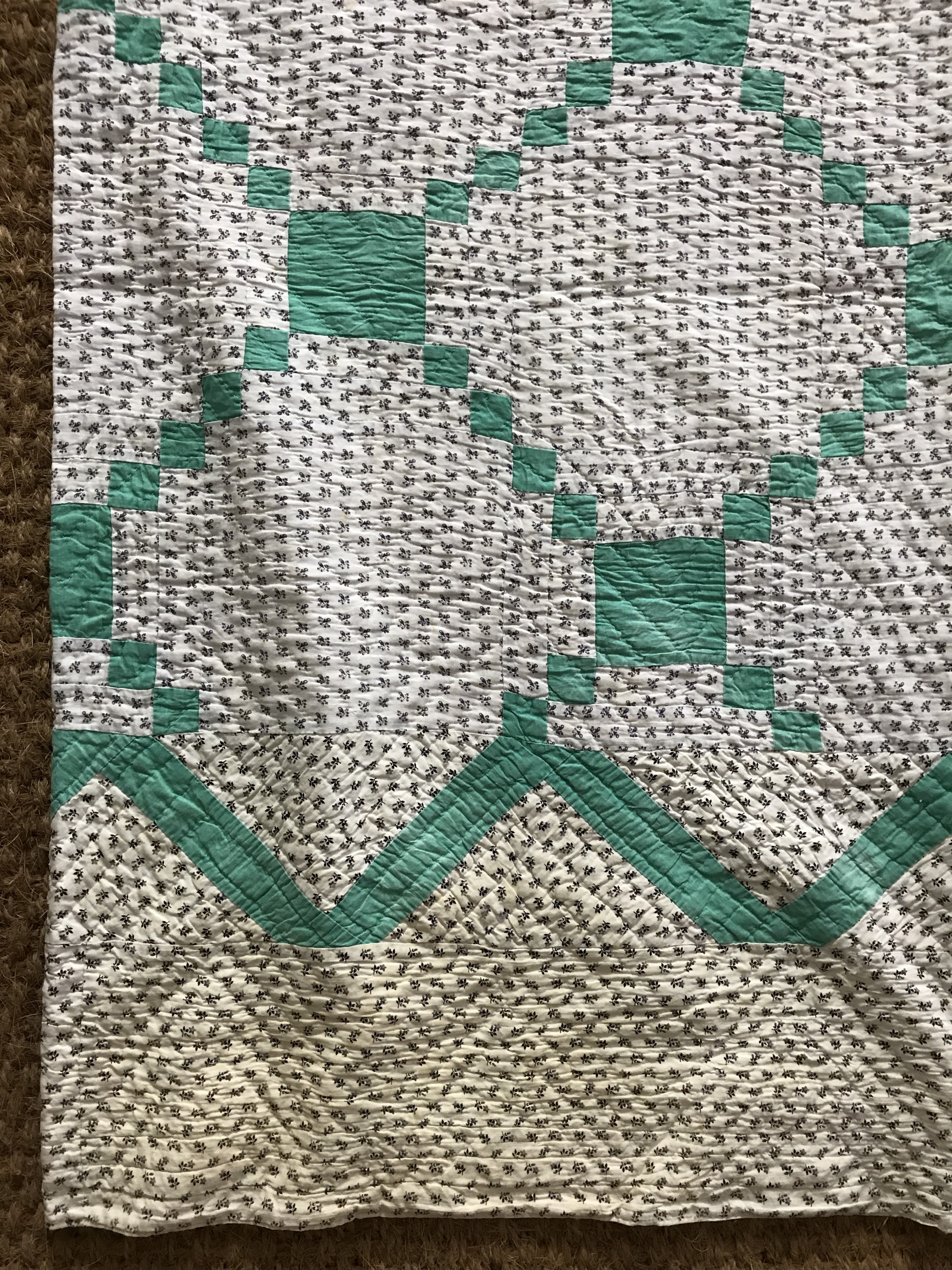 Lot 34 - An early 20th Century patchwork quilt, in a geometric diaper design incorporating mint green and