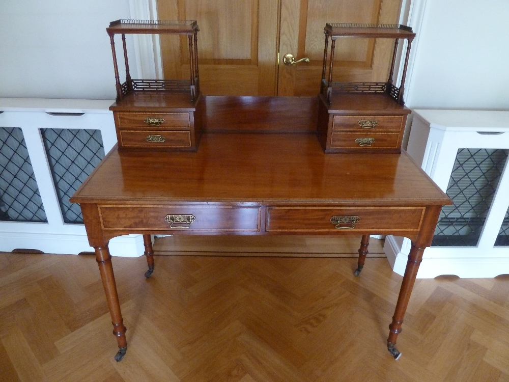 Lot 6 - A mahogany Chinese style rectangular desk with gallery on turned cylindrical legs with castors