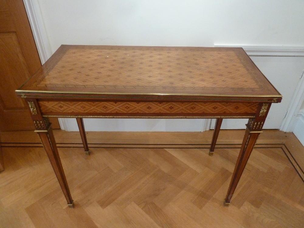 Lot 10 - A French Louis XVI style rectangular kingswood games table with gilded metal mounts on tapering