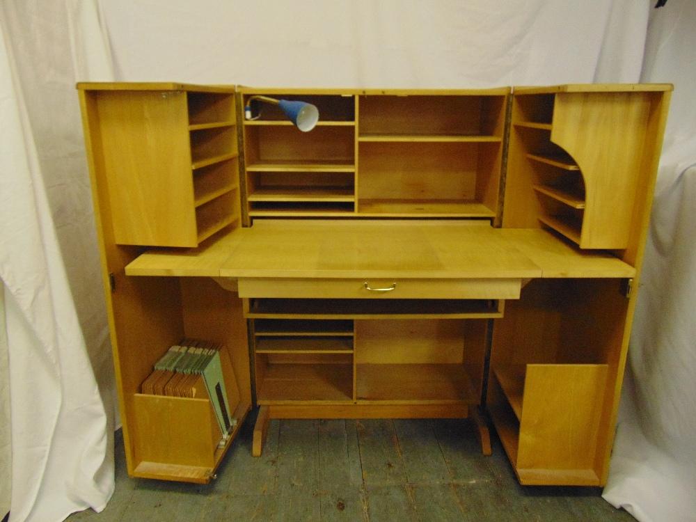Lot 4 - A 1960s light oak rectangular desk cum cupboard, the hinged doors revealing book and stationery