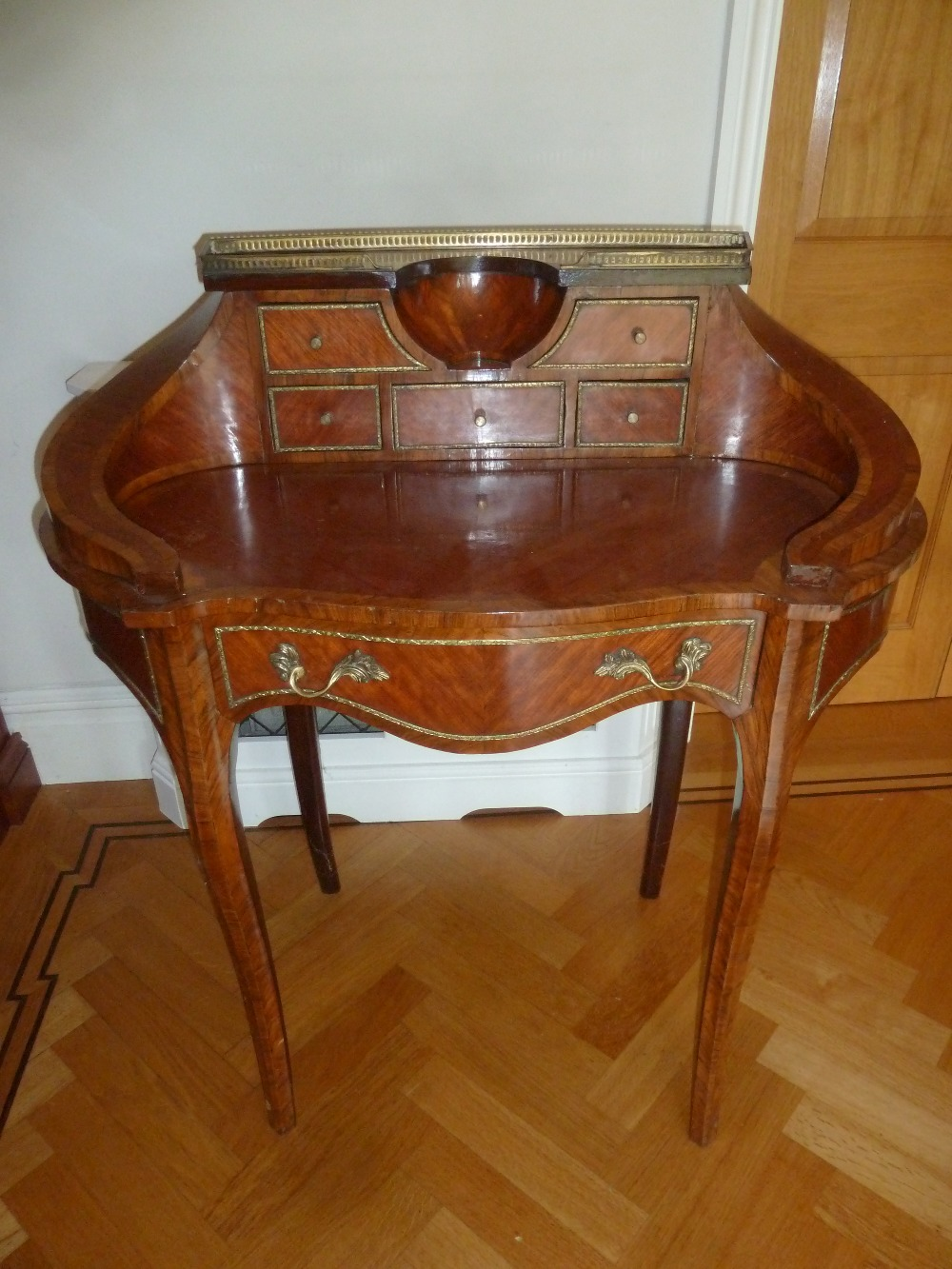 Lot 7 - A kingswood shaped oval inlaid desk with gallery and six drawers on cabriole legs