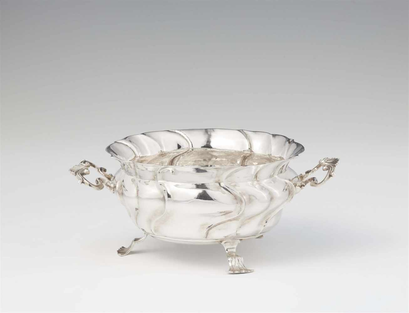 An Augsburg Rococo silver dishBombé form twist fluted dish with scroll handles resting on three