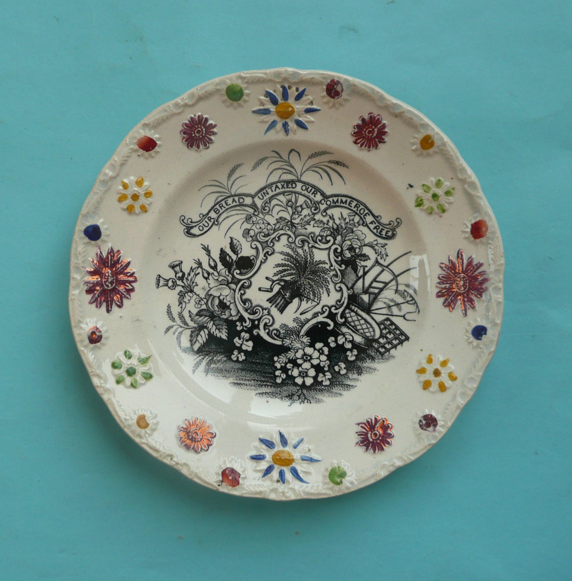 Lot 42 - Corn Laws: a nursery plate with colourful moulded border printed in black, circa 1840, 152mm (
