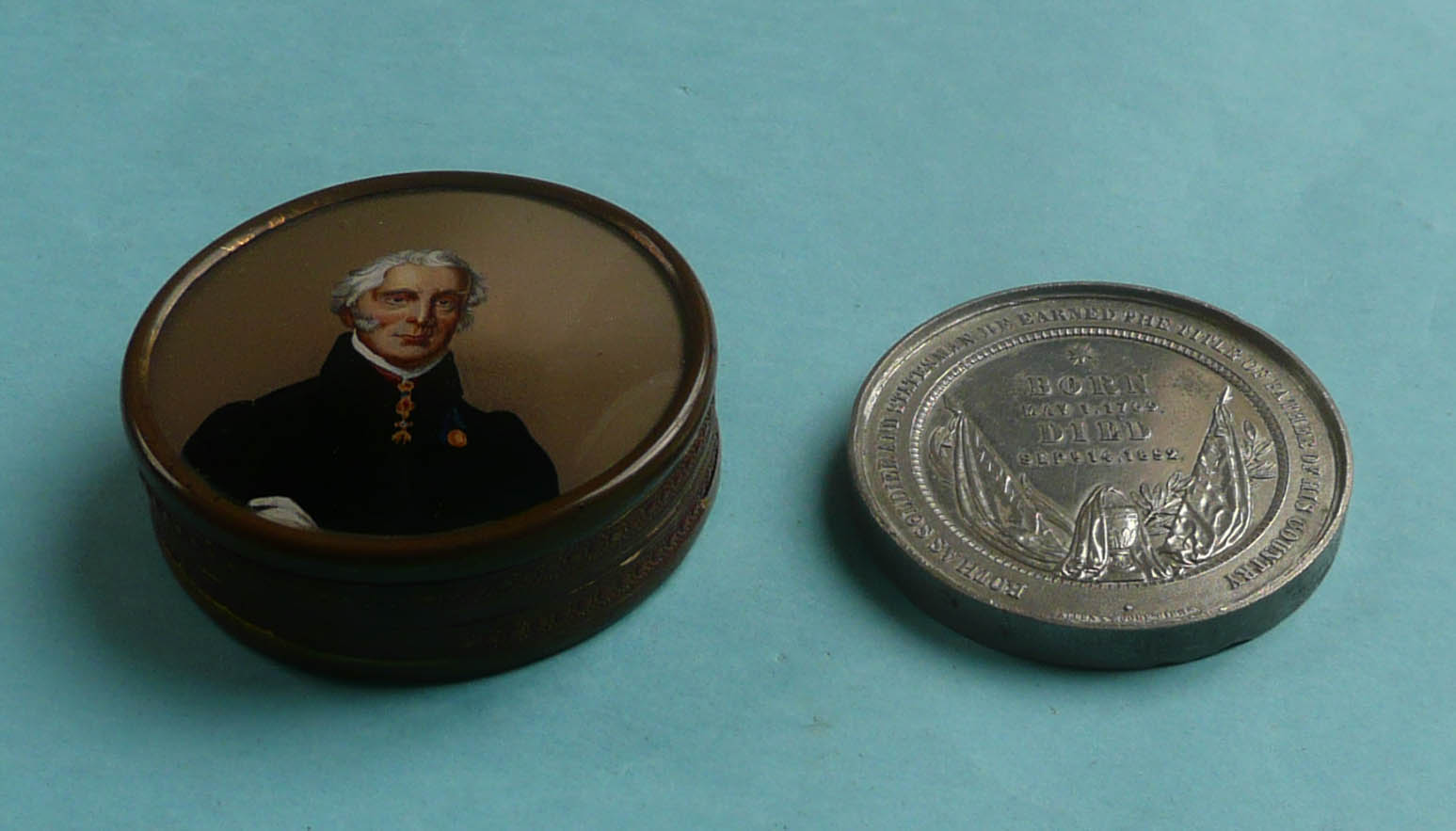 Lot 30 - Wellington: an embossed card and brass mounted circular box, the cover with a reverse glass