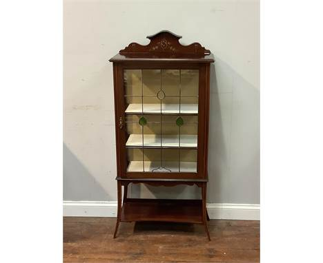 An Edwardian display cabinet with raised hand painted floral back, stained glass single door encasing a 2 shelved area on tap