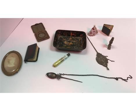 A collection of various objets de vertu, including photograph frames, spike spoons, lead soldier figure, two glass pendants,