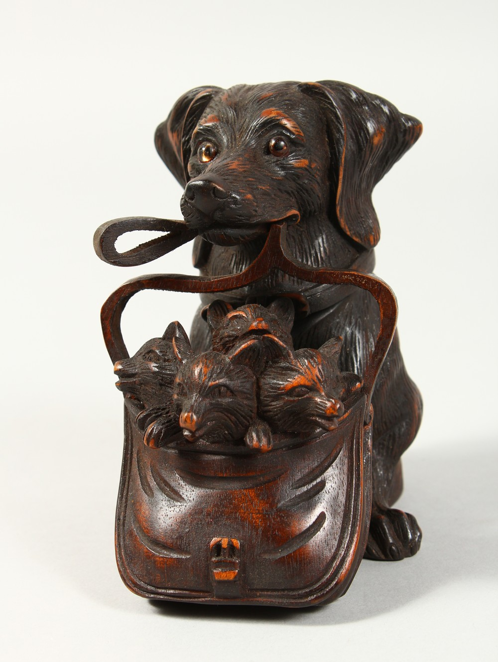 A BLACK FOREST STYLE CARVED WOOD INKWELL, modelled as a dog holding a bag of puppies in its mouth.