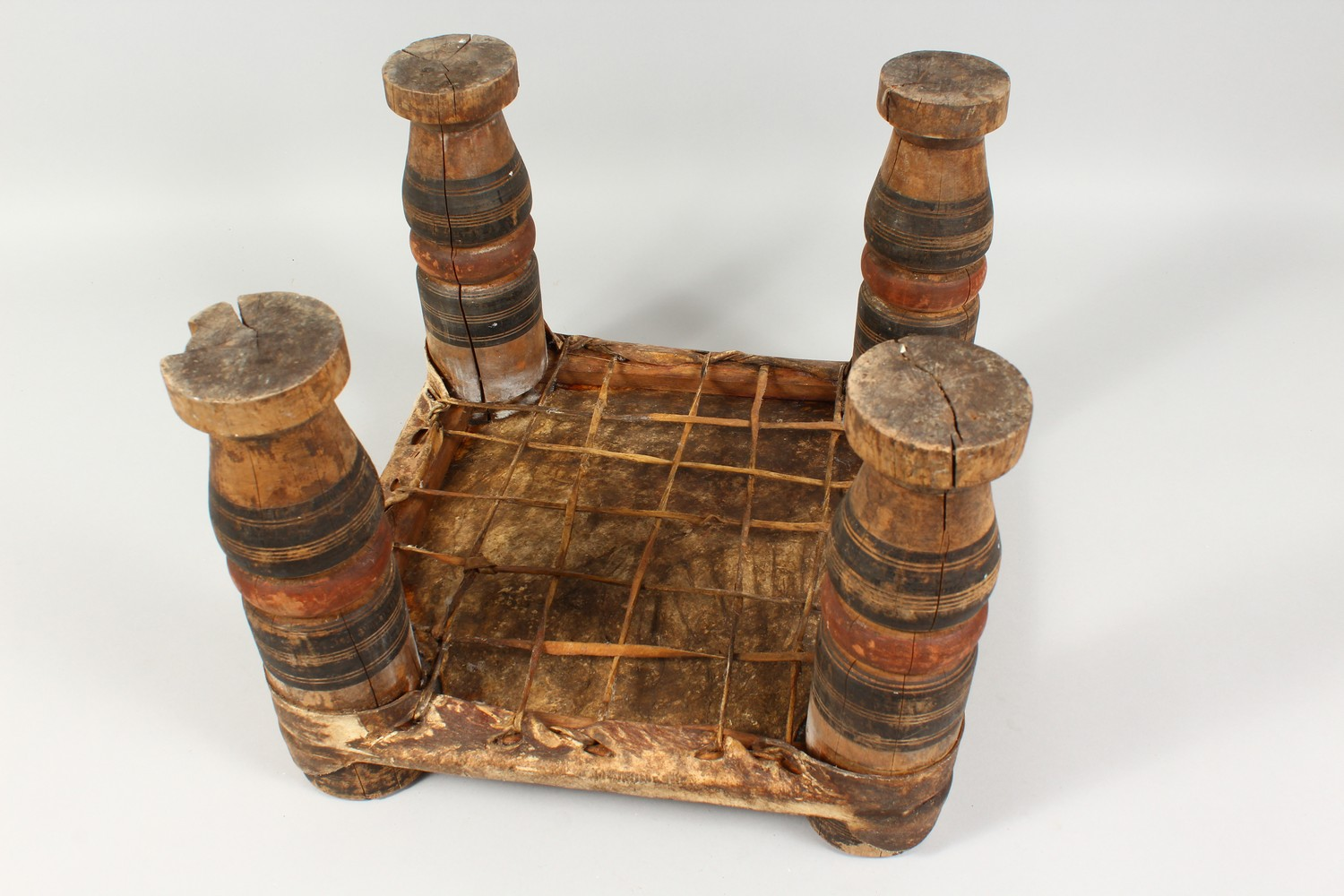 A NORTH AFRICAN PAINTED WOOD AND ANIMAL SKIN SQUARE SHAPED STOOL. 15ins wide x 11.5ins high. - Image 5 of 8